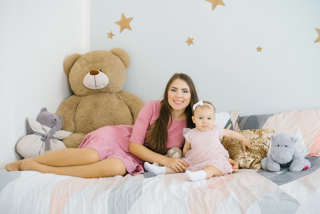 A young mother and a one-year-old daughter are resting on the bed in the children's room. happy motherhood and childhood