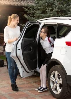若い母親が娘のために車のドアを開ける
