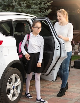 学校からの旅行の後、若い母親が娘に車のドアを開ける