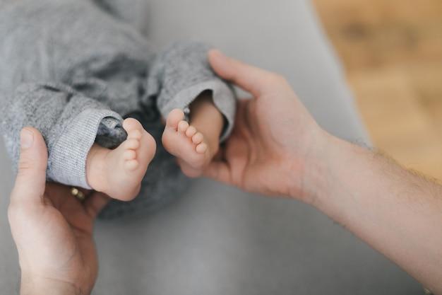 신생아의 맨발로 작은 발을 들고 젊은 어머니 또는 의사 손. 부모의 행복한 순간. 확대.