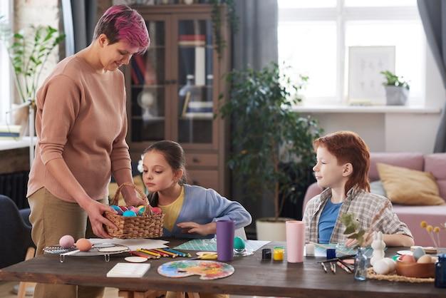 Молодая мать красит яйца вместе со своими детьми, сидя за столом в комнате