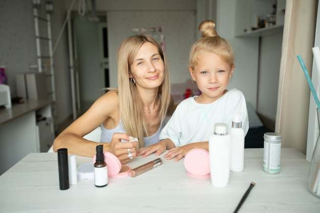 Young mother paints her little daughters nails