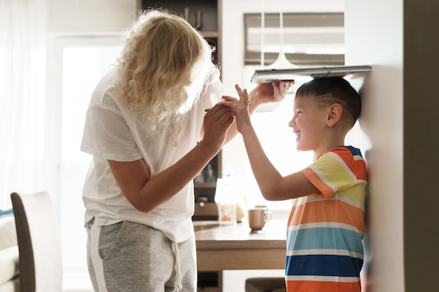 Young mother playfully measuring the height of her son