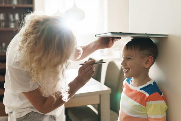 息子の身長をふざけて測定する若い母親