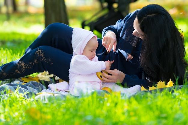 귀여운 분홍색 옷을 입고 여자 아기와 함께 가을에 정원이나 공원에서 야외에서 노는 젊은 어머니