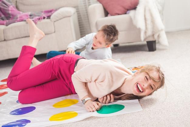 Молодая мать играет твистер с сыном. веселая семья в помещении. счастливая семья играет вместе