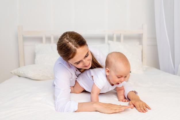 若い母親が赤ちゃんと遊ぶ6ヶ月白いベッドに横たわって、母と子の愛、母の日