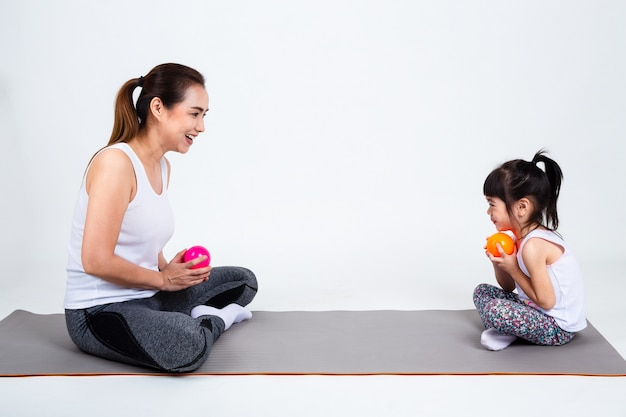Young mother playing with cute daughter on white background