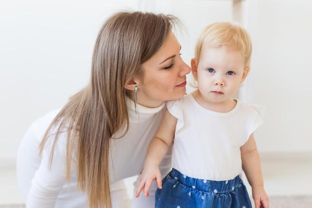 家で女の赤ちゃんと遊んでいる若い母親。母性、幼児および子供の概念。