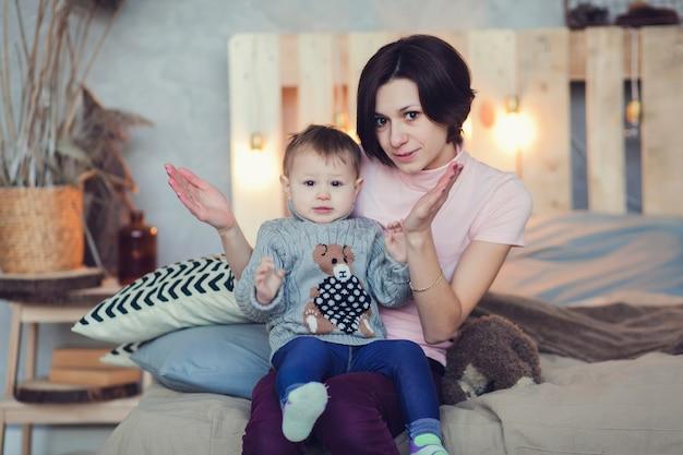 Молодая мать играет со своей девочкой в спальне