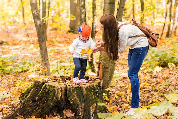 Молодая мать играет со своей дочерью в осеннем парке.