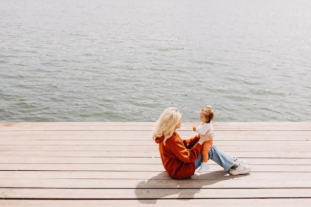 湖のそばの木の桟橋に屋外で座っている娘と遊ぶ若い母親