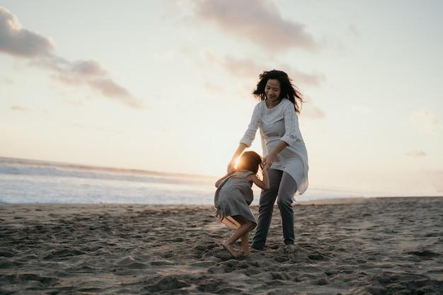 Молодая мать, играя со своей маленькой девочкой у моря