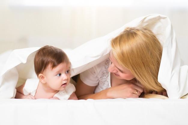 Молодая мать играет со своим новорожденным ребенком. мама кормит ребенка. счастливая женщина и новорожденная девушка расслабляются в домашнем интерьере. портрет счастливой матери и ребенка, концепции семьи дома.