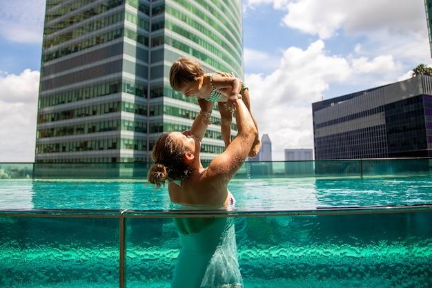メガポリス市の屋上プールで幼い娘と遊ぶ若い母親
