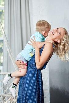 Молодая мама играет и обнимает сына.