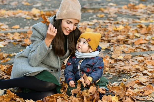 若い母親は、秋の公園で小さな子供と遊ぶ。