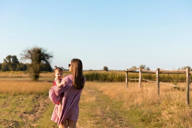 젊은 어머니는 풀밭에서 그녀의 아기와 함께 재생합니다.