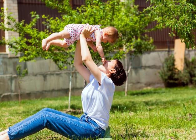 젊은 어머니는 공원의 잔디에서 아기와 함께 놀고 있습니다. 엄마와 아기