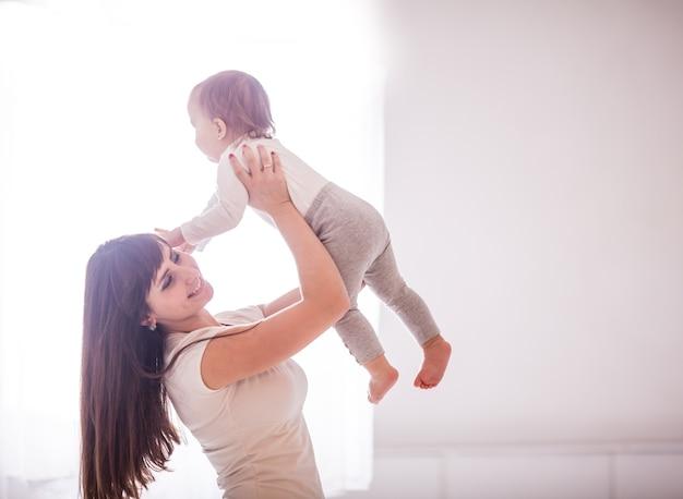 若い母親は、部屋の窓の向かいで、彼女の小さな女の赤ちゃんと遊ぶ