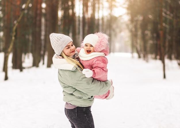 若い母親は公園で冬に彼女の小さな娘と遊んで、彼女の腕と輪を握ります