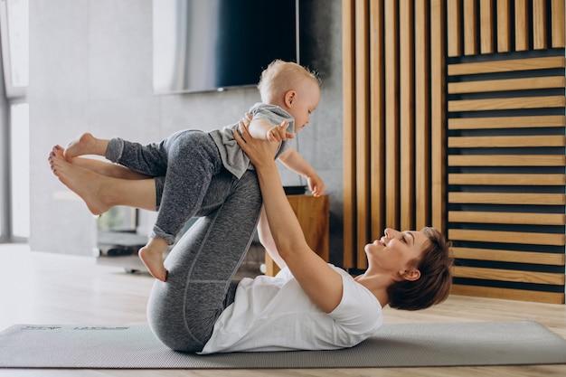 若い母親はマットの上で彼女の幼児の息子と一緒にヨガを練習します