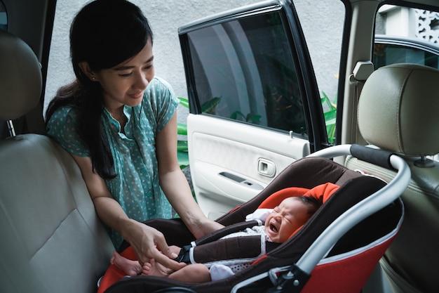 Молодая мать кладет свою дочь в автокресло