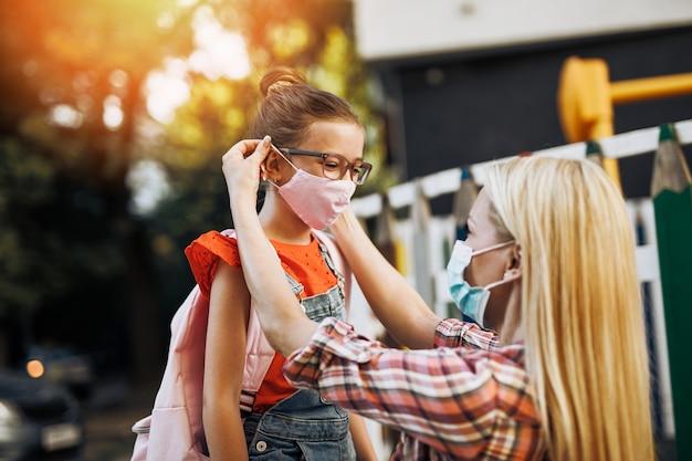 어린 딸의 얼굴에 보호 마스크를 씌운 젊은 어머니. 코로나바이러스 라이프스타일 컨셉입니다.