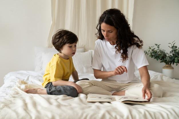 Молодая мама читала книгу милому ребенку, развлекая и развлекая сына утром на выходных дома