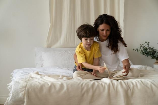 若い母親は、朝、ベッドの上のパジャマに座って寝室で小さな息子の絆と一緒に本を読みます