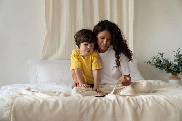 젊은 어머니는 침실에서 어린 아들과 함께 책을 읽고 아침에 잠옷을 입고 침대에 앉는다