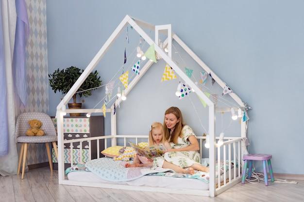 若い母親は寝室でかわいい白い家のベッドに座って彼女の3歳の幼児の女の子と本を読んで