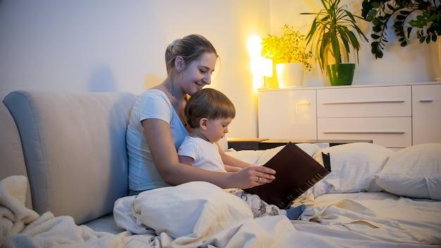 Молодая мать читает книгу сказок на ночь своему маленькому сыну.