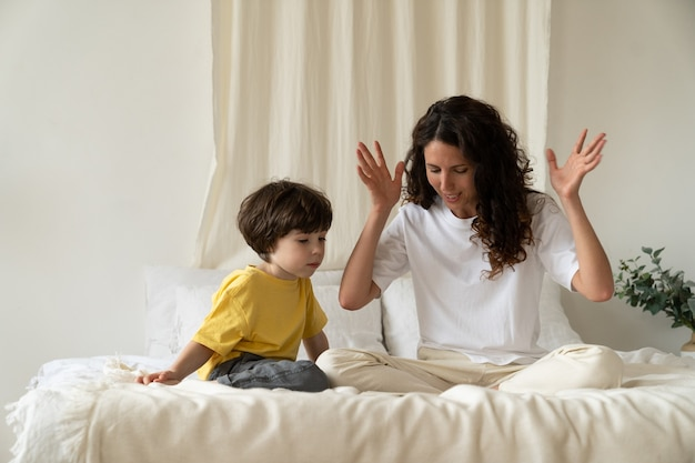 Young mother reading fairytales to little kid sitting on bed in bedroom entertain child on holiday