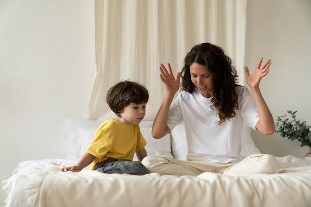 Молодая мать читает сказки маленькому ребенку, сидящему на кровати в спальне, развлекает ребенка на празднике