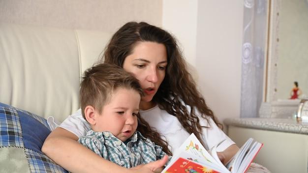 Молодая мама читает ребенку книгу перед сном.