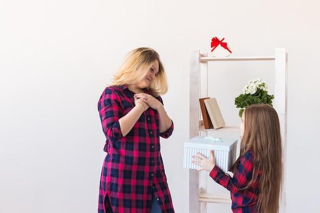 젊은 어머니는 어머니의 날에 놀란 선물을보고 입을 벌리고 흥분된 딸에게서 깜짝 놀라움을 받았습니다.