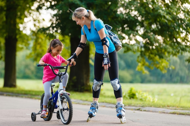 A young mother roller skating. daughter riding a bicycle