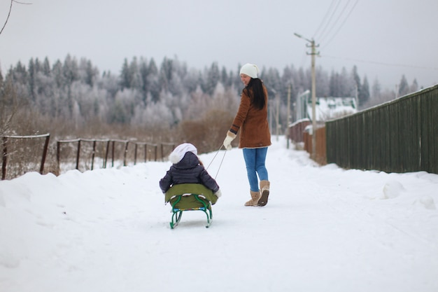 Young mother rolls her little cute daughters on a sled in winter day