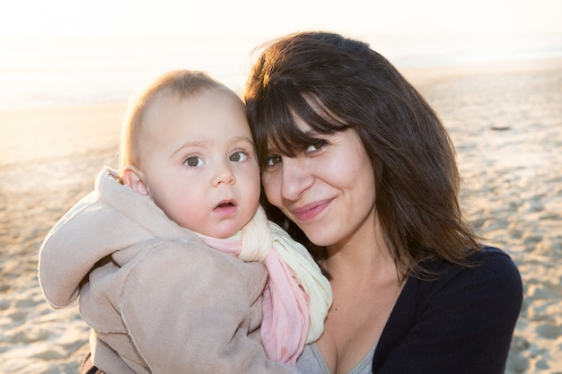Young mother on sand beach with baby girl daughter