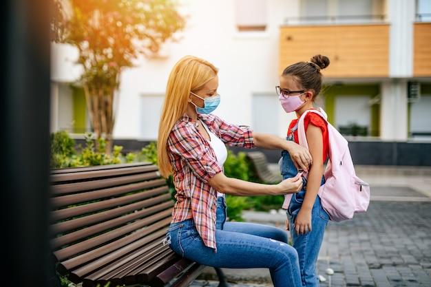校庭で顔面保護マスクをつけた幼い娘に別れを告げる若い母親。彼らは顔面保護マスクを着用しています。学校のコンセプトに戻ります。