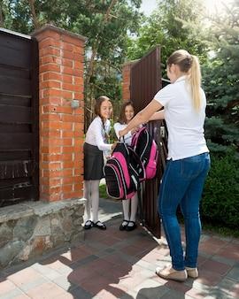 学校に行く娘たちに別れを告げる若い母親
