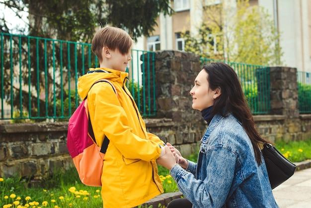 Молодая мать прощается с маленьким сыном возле школы. женщина и мальчик с рюкзаком за спиной. начало уроков. первый день в школе. мать берет сына в школу.