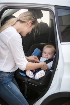 Молодая мать усаживает ребенка в автомобильное сиденье