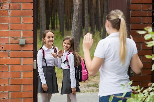 朝、2人の娘が学校に行くのを見ている若い母親