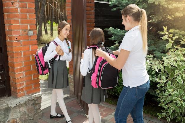 若い母親が娘を見送り、バッグをかぶるのを手伝う