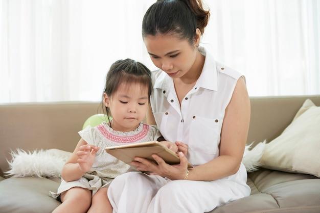 彼女の小さな娘にタブレットコンピューターで教育アプリケーションを示す若い母親