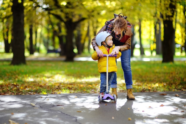 Young mother showing her toddler son how to ride a scooter in a autumn park.