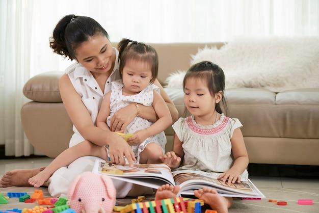 Молодая мама показывает фото в альбоме своим маленьким дочуркам, когда они вместе проводят время ...