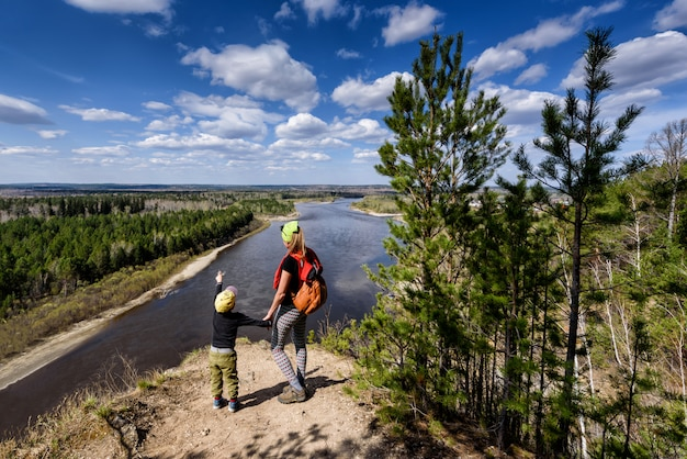 Young mother shows her child a beautiful landscape in spring irkut river with sky clouds. view from above, siberia